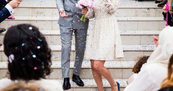 mariés sur un escalier avec invités qui lancent des confettis